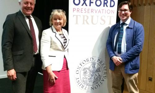 Duncan Wilson, Debbie Dance and William Whyte stand in front of the OPT logo.
